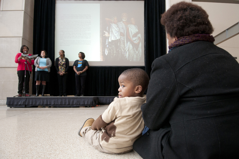 Garrison Brown, 2, and Jinai Lewis listen to a reading of the short story \