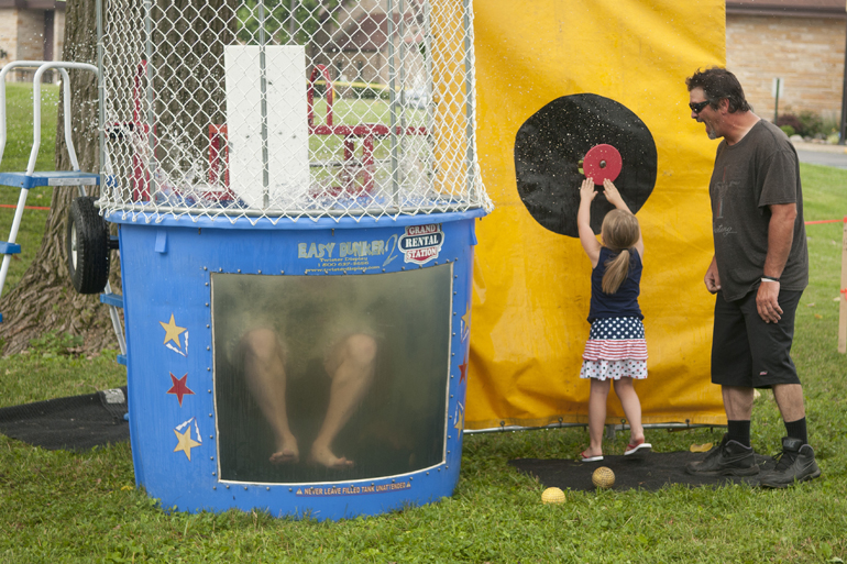 Greenwood Freedom Festival, Saturday, June 28, 2014. Breianna Harlow, 4, with her grandfather Robert McCalister, pushes a button to make Greenwood mayor Mark Myers fall into a dunk tank. The mayor was helping raise money for chemotherapy treatments for two girls at Northeast Elementary School.
