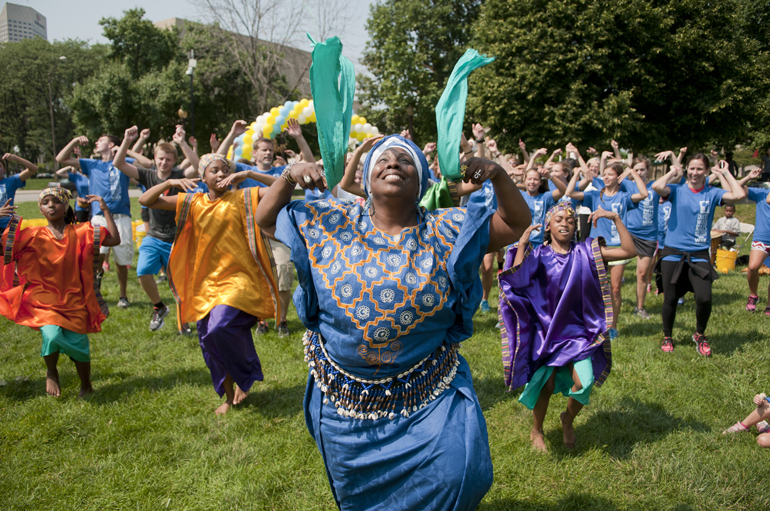 Sabra Logan, founder and director of Iibada Dance Company, leads walkers in an African welcoming dance during the third annual Walk for Water event downtown, Saturday, Aug. 2, 2014. The event raised money for a community clean-water well in Kager, Kenya. Attendees walked from American Legion Mall to the canal, filled buckets with water and walked back to the mall, simulating the path villagers without clean water have to take every day.