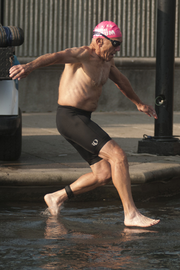 A swimmer jumps into the Indiana Central Canal to begin the Tri-Indy Triathlon, Sunday, Aug. 3, 2014. The triathlon route was centered at White River State Park and went as far north as the Major Taylor Velodrome.