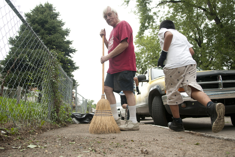 Resident Daniel Hardt sweeps the sidewalk as children play during a community clean-up on South Elder Street near Washington Street, Saturday, Sept. 6, 2014. City organizations lent volunteers and equipment to residents to renovate the high-crime area along West Washington Street.