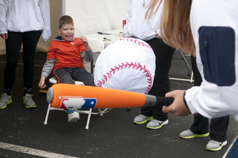 Braden Tamosaitis, 9, pitches an oversize softball to Notre Dame outfielder Megan Sorlie during the Riley Hospital for Children Neonatal Intensive Care Unit Reunion at Fairbanks Hall, Saturday, Sept. 13, 2014. Members of the Purdue and Notre Dame softball teams visited Riley to staff booths at the reunion and visit children at the Riley Hospital for Children Cancer Center.