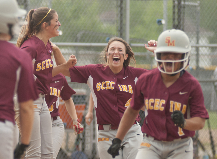 Scecina pitcher Julia Blastic (center) and other teammates celebrate as Lea Thompson (right) runs home after Justice Carmichael\'s grand-slam home run during Scecina\'s 7-4 victory over Cathedral in the high school city softball title game at Brookside Park, Saturday, May 9, 2015.